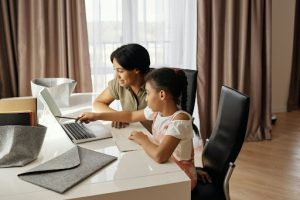 Mother helping daughter with online school learning   Luxury Homes by Brittany Corporation