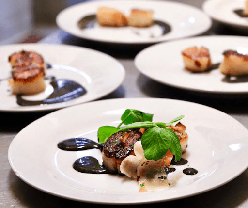 Perfectly grilled scallops with a wine reduction sauce topped with a sprigg of freshly picked basil a luxury house and lot dish for foodies | luxury homes by brittany corporation