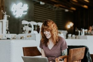Photo of a smiling woman sitting on a brown wooden chair while using her laptop - Real estate agents - Luxury Homes by Brittany