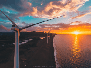 Photo of a windmill facing the sea with a golden sunset - Brittany Corporation