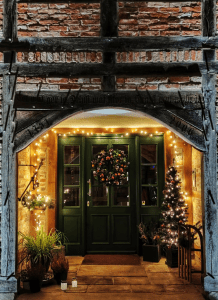 Photo of green wooden door with a Christmas wreath and lights   luxury homes by brittany corporation
