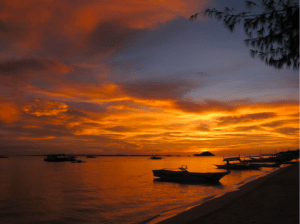 Photo of the sea and golden hour sky with boats by the shore in Western and Central Visayas where Cebuanos live - Brittany Corporation