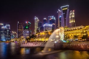 Singapore skyline at night merlion water releasing water luxury condominium behind them for vegan travel   luxury homes by brittany corporation