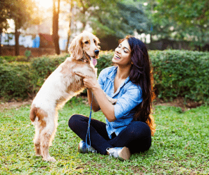 Woman playing with her blonde Cocker Spaniel in the park | Luxury Homes by Brittany Corporation