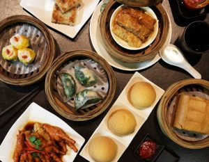 an array of steamed dimsum siomai, kutchay dumplings, chicken feet, baos, tofu skin rolls, radish cake, and steamed cake flat lay for a luxurious display of luxury masion palate | luxury homes by brittany corporation
