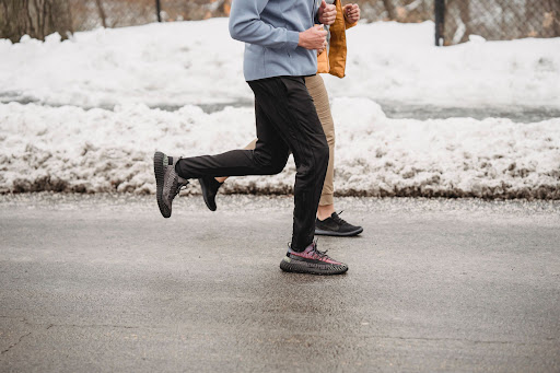 couple jogging along a snowy path wearing black and khaki jogging pants luxury homes luxury house and lots by brittany corporation | Luxury homes by Brittany corporation