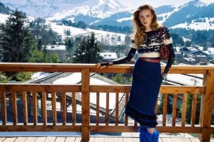 Caucasian lady wearing knitted top and blue fluffy skirt with a red bag and blue fluffy boots in front of a mountain   luxury homes by brittany corporation