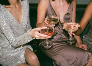 lady wearing silver dress and lady wearing brown metallic dress toast margaritas with an unseen thrird person in a party in a luxury homes by brittany corporation   luxury homes by brittany corporation