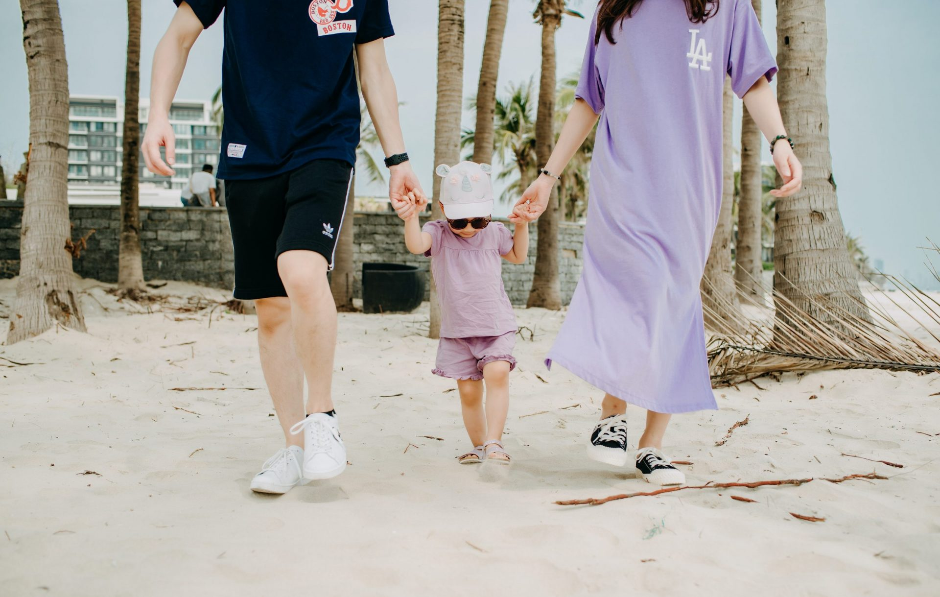 light skinned couple with a baby on the beach enjoying a luxury travel with kids woman wearing a purple dress man wears black | luxury homes by brittany corporation