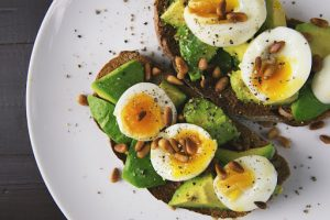 omega rich avocado toast with soft boiled egg cut in half with freshly ground black pepper on a table in a luxury condominium by brittany cororation   luxury homes by brittany corporation