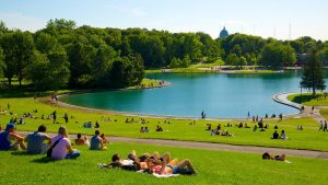 people lying down on the green grass overlooking the lake in mount royal park luxury condos near it | Luxury homes by brittany corporation
