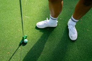 Green putter with a green golf ball | luxury homes by Brittany corporation