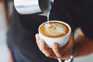 Man pouring milk into coffee to create latte art