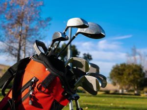 a red golf bag with different types of golf clubs. | Luxury homes by Brittany corporation