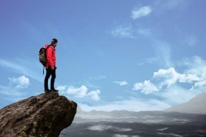 Mountain hiker in red jacket stands by the edge of a cliff   luxury homes by brittany corporation