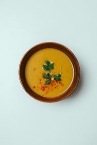 orange soup in a red bowl on a blue table in a luxury house and lot   luxury homes by brittany corporaton
