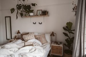 unmade double bed with white sheets three brown pillows and a fleece comforter with two end tables on either side of the bed plants on a shelf a mirror and lamps in a luxury house and lot   luxury homes by brittany corporation