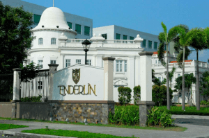 Enderun entrance white half wall with luxury gold enderun plate and logo white buildings behind the logo | luxury homes by brittany corporation