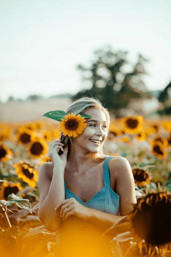 Caucasian woman in Sunflower Garden wearing a blue dress taking a photo for the golden hour   Luxury Homes by Brittany Corporation