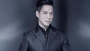 Francis Libiran in a geometric black suit staring at the camera with metallic gray background luxury house and lot