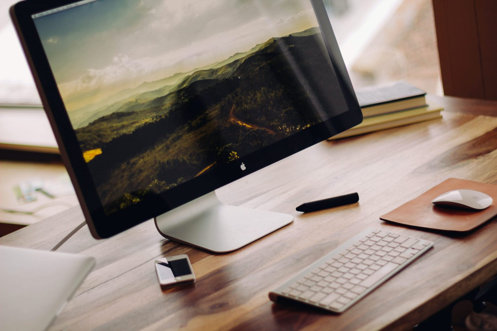 Photo of iMac on top of a wooden desk | Luxury Homes by Brittany Corporation