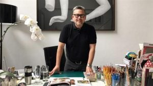 Rajo Laurel in black polo shirt in luxury home table with clutter man wearing glasses with expensive painting behind him | Luxury Homes by Brittany Corporation