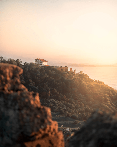 The setting sun shining on a hilltop house   Luxury Homes by Brittany Corporation