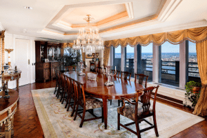cityspire new york luxury condominium long wooden table and 8 chairs in the middle with a chandelier and white ceiling white carpet | Luxury Homes by Brittany Corporation
