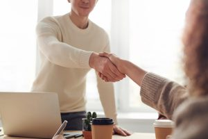 man in white shaking hands with woman in brown closing luxury homes   Luxury Homes By Brittany Corporation