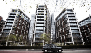 one hyde park london luxury condominium low rise luxury condo building with black car in front and trees | Luxury Homes by Brittany Corporation