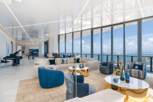 one thousand museum luxury condominium grand piano on the left floor to ceiling glass windows sofa lounge chaise | Luxury homes by brittany corporation