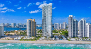 residences by armani casa luxury condominium by the bear blue green water blue skies and small luxury homes around | Luxury Homes by Brittany Corporation