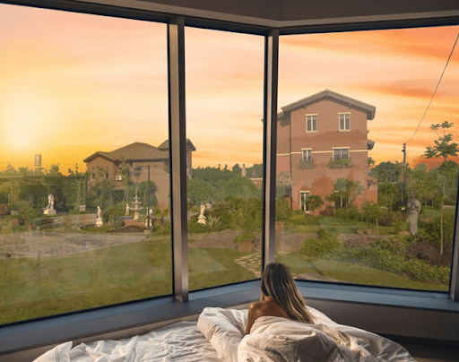 woman on bed overlooking portofino Alabang luxury house and lot properties | luxury homes by brittany corporation